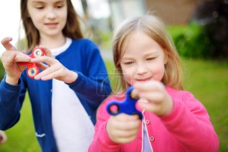 Photo for Two happy sisters playing with colorful fidget spinners on the playground. Popular stress-relieving toys for kids - Royalty Free Image