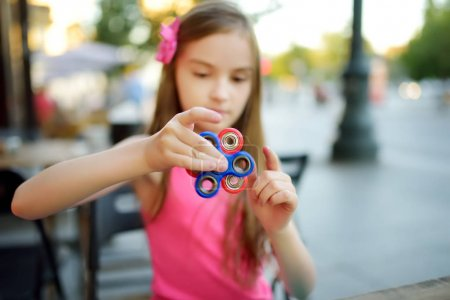 girl playing with colorful fidget spinner