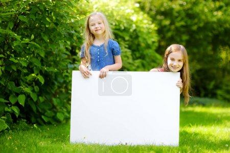 Photo pour Deux jolies petites sœurs tenant un grand tableau blanc vierge sur une journée d'été chaude et ensoleillée en plein air - image libre de droit