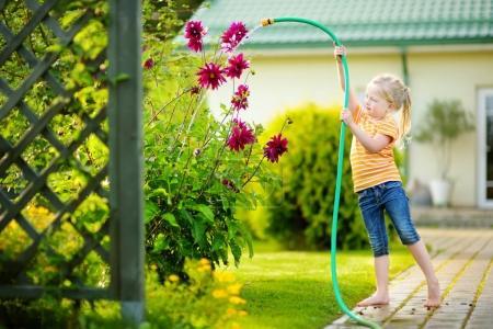 Photo pour Adorable petite fille arrosant des fleurs violettes en utilisant un tuyau d'arrosage. Enfant et fleurs dans le jardin d'été, joyeuses vacances - image libre de droit