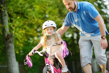 Photo for Father teaching his cute little daughter to ride a bicycle. Child learning to ride a bike. Family activity in summer - Royalty Free Image