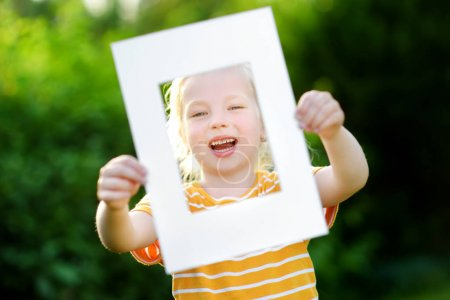 little girl holding white frame