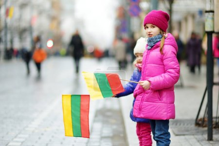 Two adorable little sisters celebrating Lithuanian Independence Day holding tricolor Lithuanian flags in Vilnius