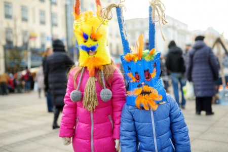 Two cute little girls with frightening masks during the celebration of Uzgavenes, a Lithuanian annual folk festival taking place seven weeks before Easter
