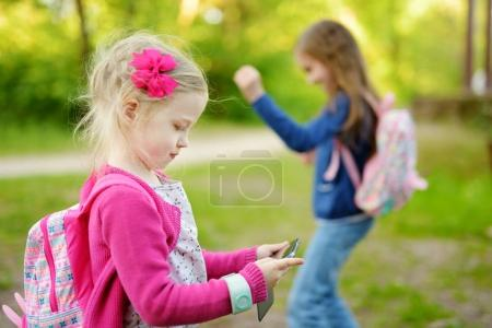 Two cute little sisters playing outdoor mobile game on their smart phones. Modern addictive multiplayer location-based games.