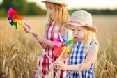 Adorable girls playing with colorful pinwheels in wheat field on warm and sunny summer evening. Cute little children in rye field on sunset.