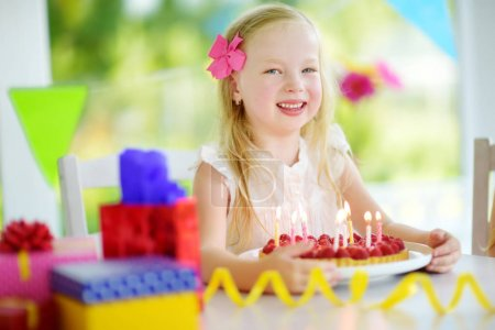 Adorable girl having birthday party at home, blowing candles on birthday cake. Kids birthday party with colorful decorations, gifts and banners.