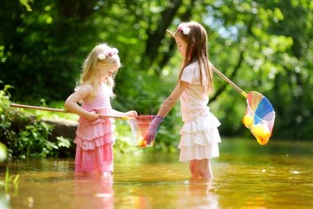 cute little sisters playing in river