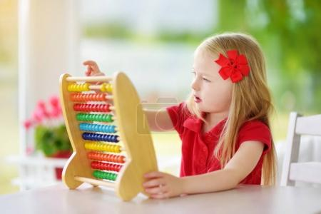 little girl playing with wooden abacus