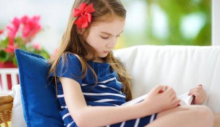 girl reading book in living room