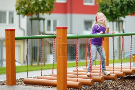 Cute little girl having fun on a playground outdoors in summer. Sport activities for kids.