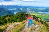 Two sisters enjoying picturesque views from the Tegelberg mountain, a part of Ammergau Alps, located nead Fussen town, Bavaria, Germany.