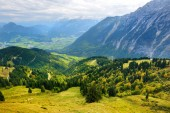 Breathtaking lansdcape of mountains, forests and small Bavarian villages in the distance. Scenic view of Bavarian Alps with majestic mountains in the background. Bavaria, Germany.