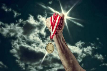 hand with a medal on sky background