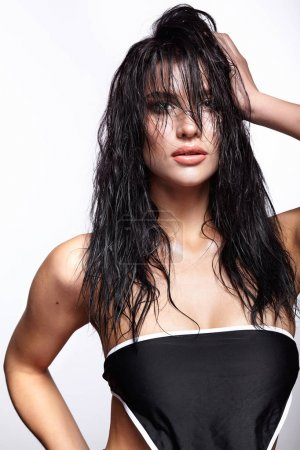 Portrait of a young brunette woman with shining wet make-up and