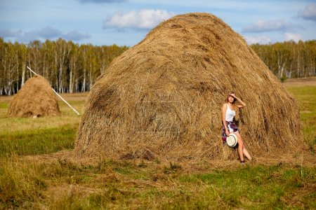 Young blonde country girl in hat near haystacks...