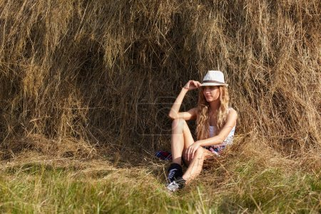 Young blonde country girl in hat sit near haystack...