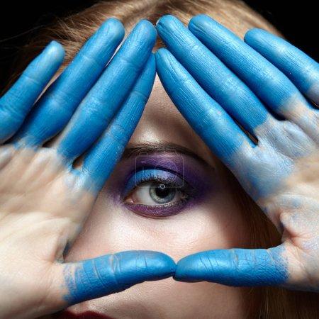 Photo pour Œil de la Providence, symbole de pyramide œil fait des mains et visage de femme avec de la peinture bleue sur les doigts - image libre de droit