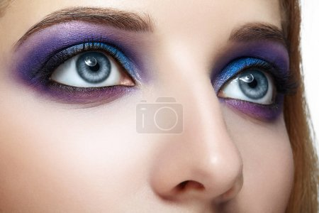 Female face eye with blue and violet makeup