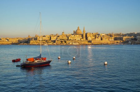 A yacht moored in the Marsamxett harbor with the Valletta capita