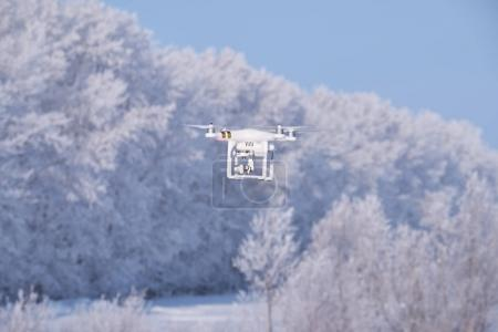 Copter Phantom on forest under snow background in winter season