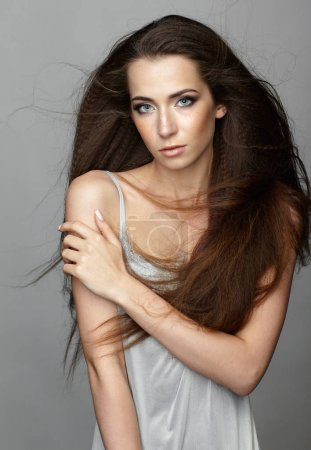 Beauty portrait of young woman. Brunette girl with long dishevel