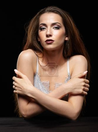 Beauty portrait of young woman sit at the black table. Brunette
