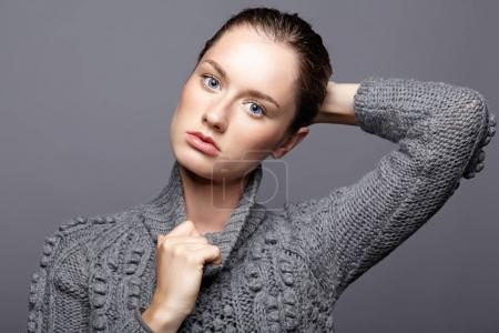 Beauty portrait of young woman in gray wool sweater. Brunette gi