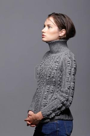 Photo for Beauty portrait of young woman in gray wool sweater. Brunette girl with bright blue eyes and day female makeup. - Royalty Free Image