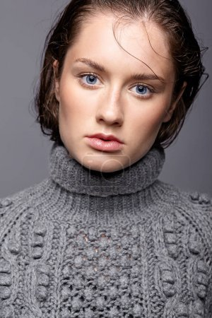 Beauty portrait of young woman in gray wool sweater. Brunette gi