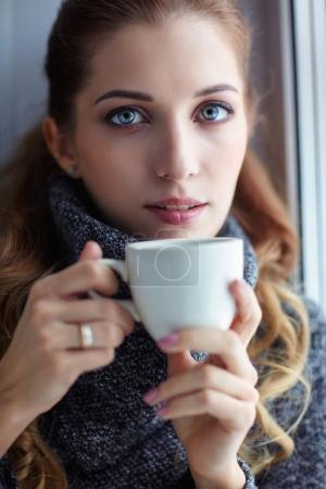 Young pretty woman in wool sweater with white coffee cup in hand