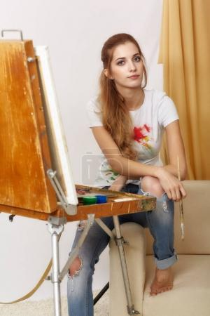Painter female with wooden sketchbook sitting on sofa and painti