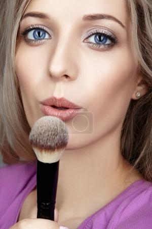 Blonde beauty female stylist  blows on makeup brush