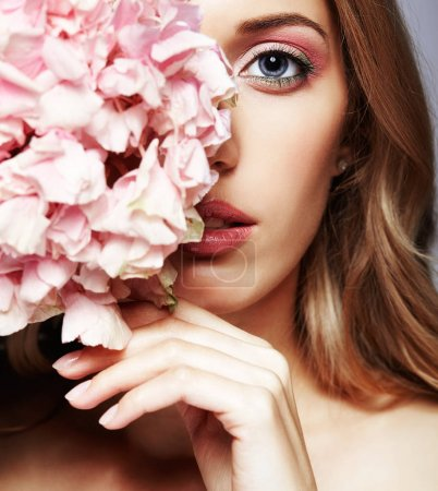 Photo for Closeup portrait of young beauty female face with blond hair and hydrangea bouquet flowers near face - Royalty Free Image