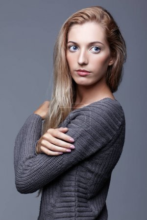 Portrait of young woman in gray woolen sweater. Beautiful girl p