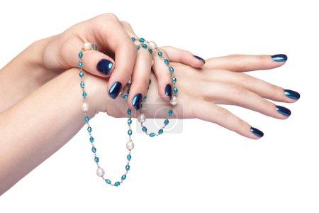 Femme les mains avec des perles de la bijouterie et brillants ongles manucure isol
