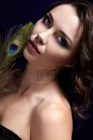 Portrait of beautiful brunette woman on black background and pea