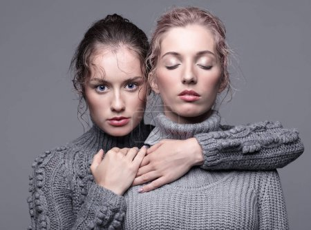 Two young women in gray sweaters on grey background. Beautiful g