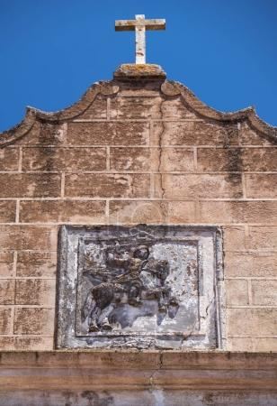 Pediment of Santiago church topped by cross and de...