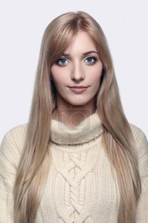 Photo pour Belle blonde jeune femme vêtue de pull en cachemire blanc grand sur fond gris - image libre de droit