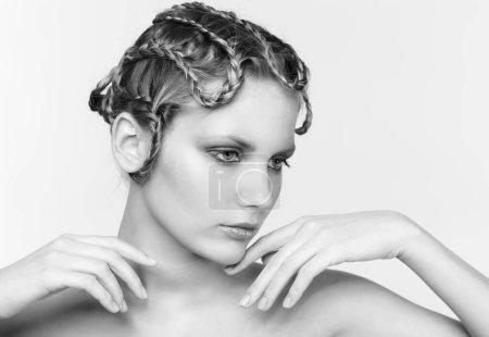 Photo pour Portrait noir et blanc dans le ton haut clé de belle jeune femme blonde foncée avec tresse créative coiffure touchant son menton - image libre de droit