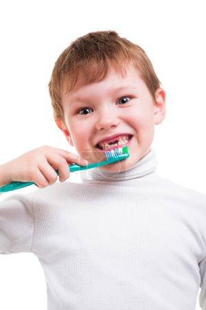 Photo pour Petit roux garçon montrant le manque de deux dents de bébé et tenant brosse à dents isolée sur fond blanc - image libre de droit