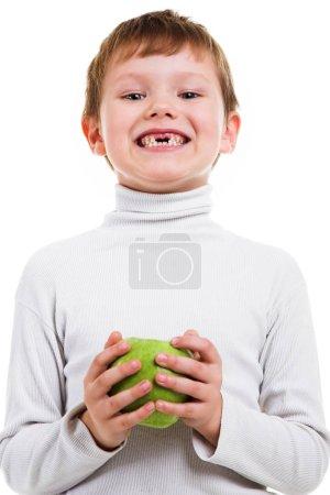Photo pour Garçon petit fuligule à tête rouge montrant l'absence de deux dents de bébé et tenant une pomme verte isolée sur fond blanc - image libre de droit