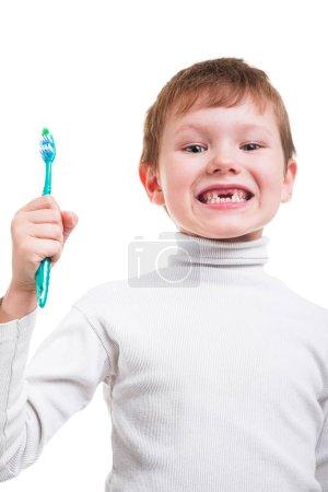 Photo pour Garçon petit fuligule à tête rouge montrant l'absence de deux dents de lait et de tenir la brosse à dents isolé sur fond blanc - image libre de droit