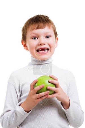 Photo pour Petit roux garçon montrant le manque de deux dents de bébé et tenant pomme verte isolé sur fond blanc - image libre de droit