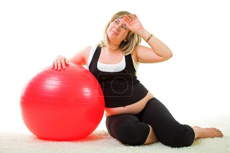 Pregnant woman with red gymnastic ball