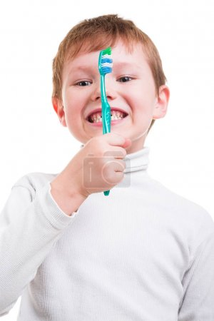 Photo pour Petit garçon roux tenant la brosse à dents isolé sur fond blanc - image libre de droit