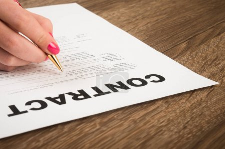 Photo pour Mains de femme d'affaires avec un stylo, signature d'un contrat sur fond en bois - image libre de droit