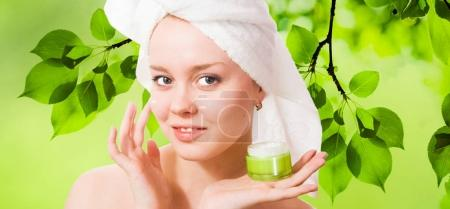 woman applying cosmetic cream on skin