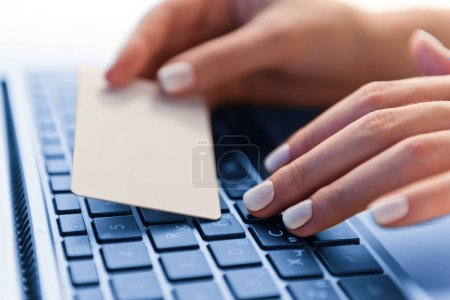 Close up of female hand holding credit card over computer keyboard
